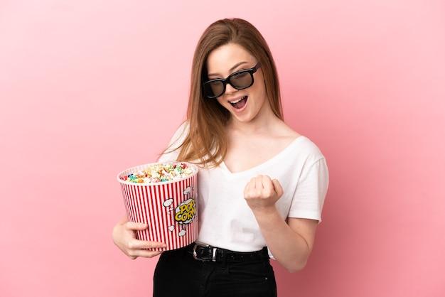 Teenager-mädchen über isoliertem rosa hintergrund mit 3d-brille und hält einen großen eimer popcorn