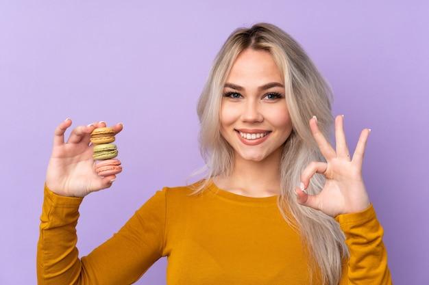 Teenager-mädchen über lila wand, die bunte französische macarons hält und ok zeichen mit den fingern zeigt