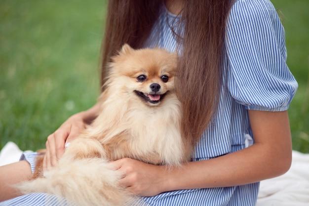 Teenager-mädchen umarmt kleinen hund in einem park im freien