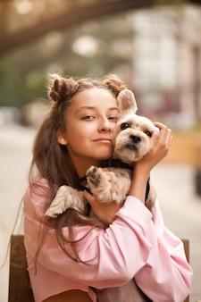 Teenager-mädchen umarmt kleinen hund in einem park im freien.