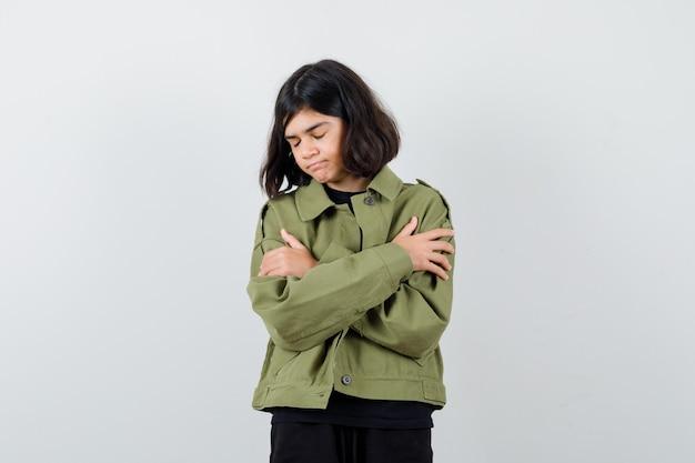 Teenager-mädchen umarmt sich in t-shirt, grüner jacke und sieht friedlich aus, vorderansicht.