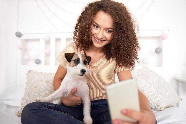 Teenager-mädchen und ihr hund machen ein selfie