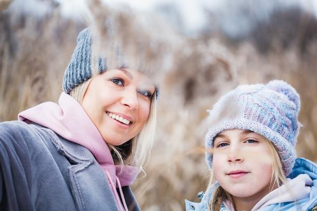 Teenager-mädchen und ihre mutter auf dem feld im winter