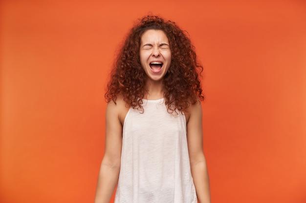 Teenager-mädchen, unglücklich aussehende frau mit lockigem ingwerhaar. tragen einer weißen schulterfreien bluse. mit geschlossenen augen laut schreien. schrei vor wut. stehen sie isoliert über orange wand