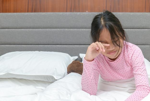 Teenager-mädchen weinen und traurig auf dem bett in ihrem schlafzimmer-, problem- und emotionskonzept