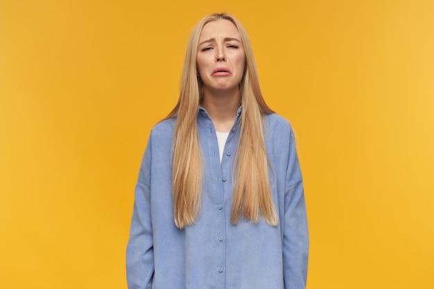 Teenager-mädchen, weinende frau mit blonden langen haaren. blaues hemd tragen. menschen- und emotionskonzept. sehr verärgert über etwas, schluchzend. beobachten in der kamera, isoliert über orange hintergrund