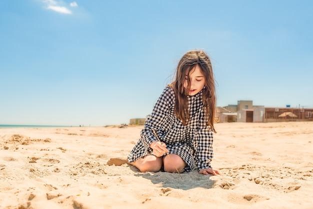 Teenager-mädchen zeichnet mit einem stock auf den sand am strand am meer. gehen sie zum traumkonzept. teenager