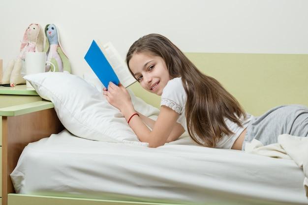 Teenager-mädchen zu hause liest ein buch auf dem bett in ihrem zimmer