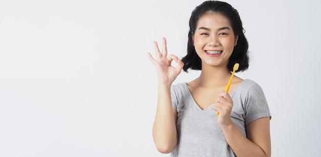 Teenager-mädchenlächeln der zahnspange, das zahnbürste hält. weiße zähne mit blauen zahnspangen. zahnpflege. asiatin mit kontaktlinse und kieferorthopädischem zubehör. kosmetische zahnmedizin.