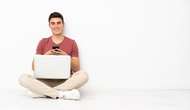 Teenager-mann, der auf dem flor mit seinem laptop sitzt, der eine nachricht mit dem handy sendet