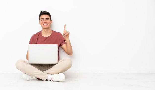 Teenager-mann, der auf dem flor mit seinem laptop sitzt, der einen finger im zeichen des besten zeigt und hebt