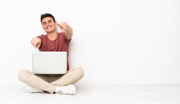 Teenager-mann, der auf der flor mit seinem laptop sitzt, zeigt finger auf sie, während sie lächeln