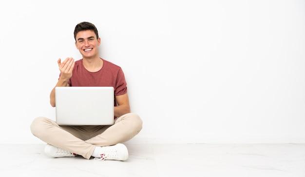 Teenager mann sitzt auf der flor mit seinem laptop einladend, mit der hand zu kommen. schön, dass du gekommen bist