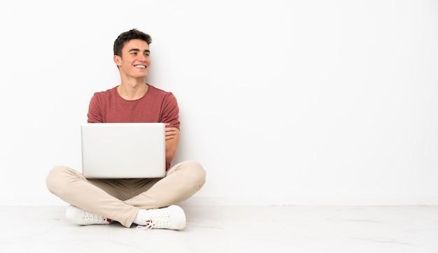 Teenager mann sitzt auf der flor mit seinem laptop glücklich und lächelnd