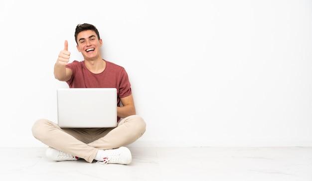 Teenager mann sitzt auf der flor mit seinem laptop mit daumen hoch, weil etwas gutes passiert ist