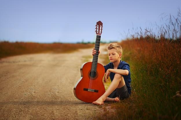 Teenager mit akustikgitarre auf landstraße.