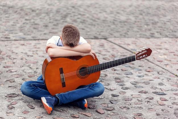 Teenager mit akustischer gitarre und kopfhörern, die im park sitzen.