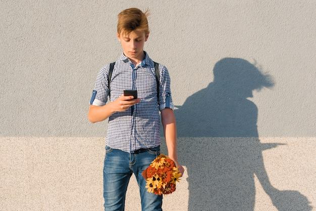 Teenager mit blumenstrauß, text auf smartphone lesend
