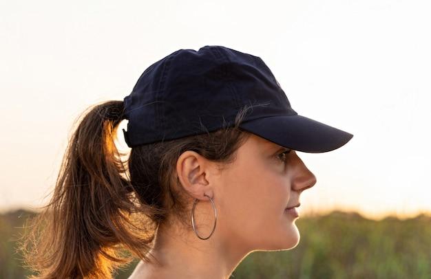 Teenager mit dunkelblauer baseballmütze bei sonnenuntergang. halbes gesicht des jugendlich mädchens. kappenmodell