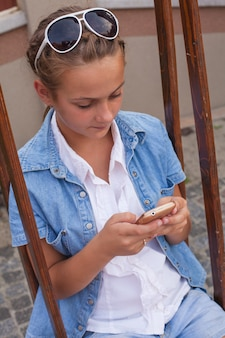 Teenager mit gadget sitzt auf der schaukel