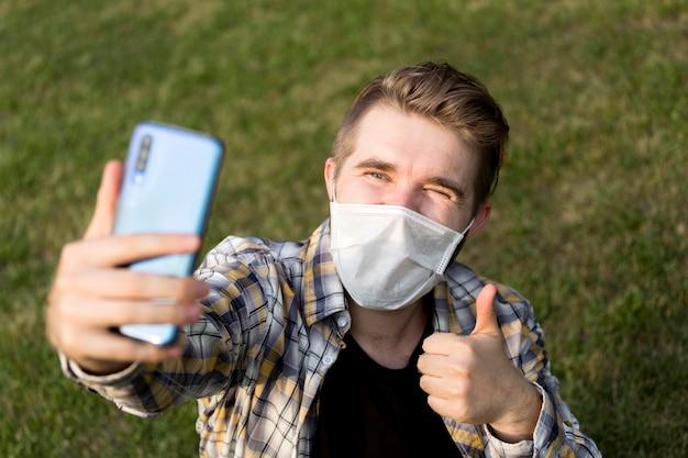 Teenager mit gesichtsmaske, die ein selfie nimmt