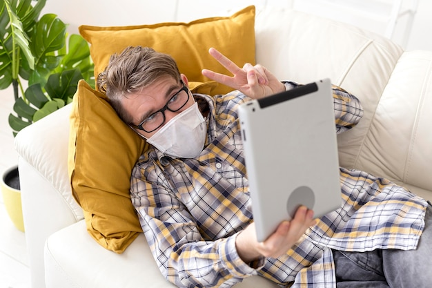 Teenager mit gesichtsmaske, die tablette hält