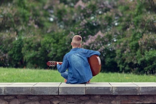 Teenager mit gitarre, die auf den stufen im park draußen sitzt. rückansicht.