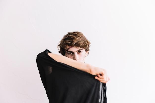 Teenager mit grimmigem und schwarzem mantel halloweens