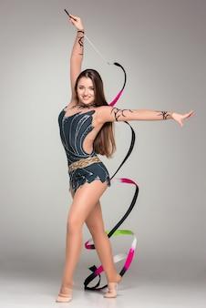 Teenager mit ihren haaren macht gymnastiktanz mit farbigem band auf grauem hintergrund