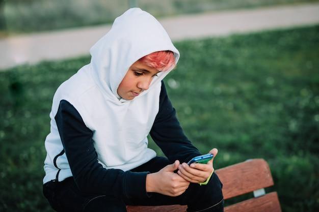 Teenager mit kapuze, der das handy in einem park betrachtet
