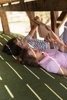 Teenager mit lehrbüchern auf gras zu studieren