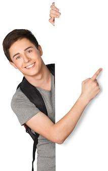 Teenager mit rucksack, der auf leeres weißes schild zeigt