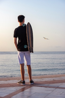 Teenager mit seinem langen brett in der promenade