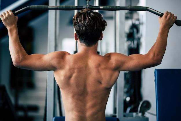 Teenager ohne t-shirt im fitnessstudio trainiert für seinen rücken - mann trainiert hart mit gewichten, um ein fitness- und ein gesunder lebensstil für den mann zu sein