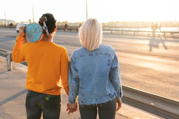 Teenager-paar händchen haltend und blick auf einen schönen sonnenuntergang in einer stadt
