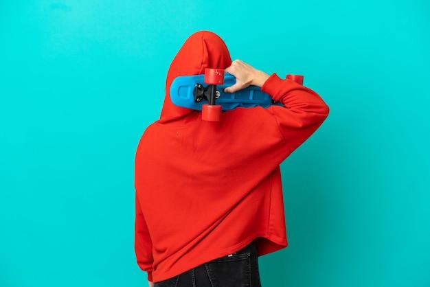 Teenager rothaarige mädchen auf blauem hintergrund mit einem schlittschuh in der hinteren position isoliert