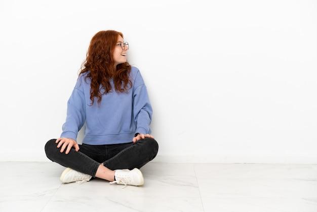 Teenager rothaarige mädchen auf dem boden sitzend isoliert auf weißem hintergrund lachend in seitenlage
