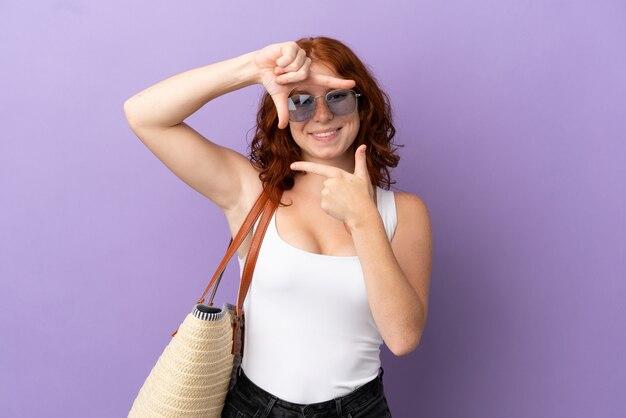 Teenager rothaarige mädchen hält eine strandtasche auf lila hintergrund fokussierung gesicht isoliert. rahmensymbol