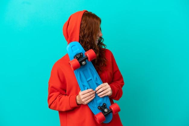 Teenager rothaarige mädchen isoliert auf blauem hintergrund mit einem schlittschuh mit glücklichem ausdruck