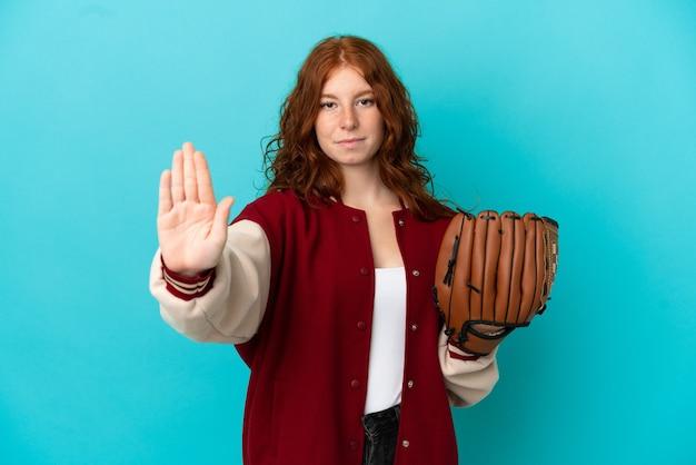 Teenager rothaarige mädchen mit baseballhandschuh auf blauem hintergrund isoliert machen stoppgeste
