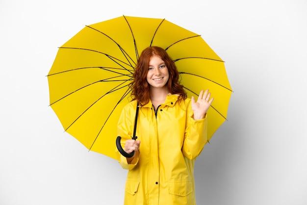 Teenager rothaarige mädchen regenfesten mantel und regenschirm isoliert auf weißem hintergrund grüßend mit der hand mit glücklichem ausdruck