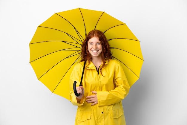 Teenager rothaarige mädchen regenmantel und regenschirm isoliert auf weißem hintergrund lächelt viel