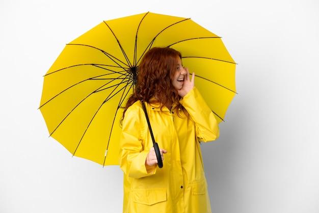 Teenager rothaarige mädchen regenmantel und regenschirm isoliert auf weißem hintergrund schreien mit weit geöffnetem mund zur seite