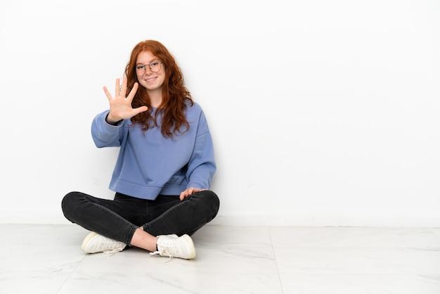 Teenager rothaarige mädchen sitzt auf dem boden isoliert auf weißem hintergrund und zählt fünf mit den fingern