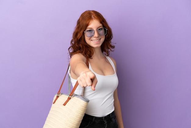 Teenager rothaariges mädchen, das eine strandtasche isoliert auf lila hintergrund hält, zeigt mit einem selbstbewussten ausdruck mit dem finger auf dich