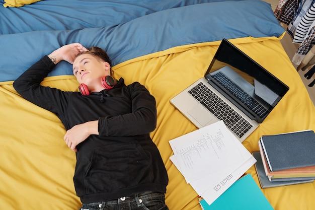 Teenager ruht müde auf dem bett, nachdem er zu hause programmieren studiert hat