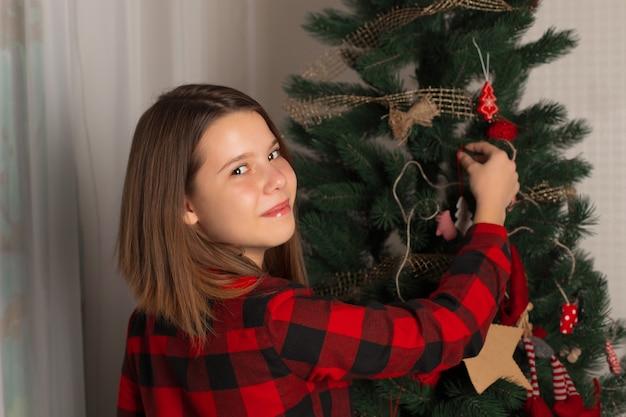 Teenager schmückt den weihnachtsbaum mit neujahrsspielzeug