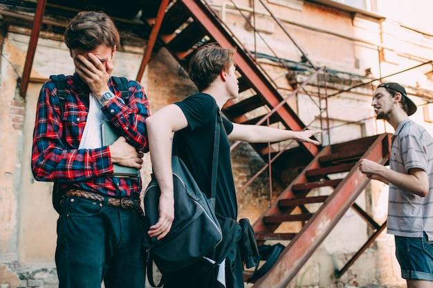 Teenager schützt seinen freund vor aggressivem tyrann. soziale jugendprobleme. erschrockener weinender intelligenter junge echtes freundschafts-loyalitäts- und support-konzept.