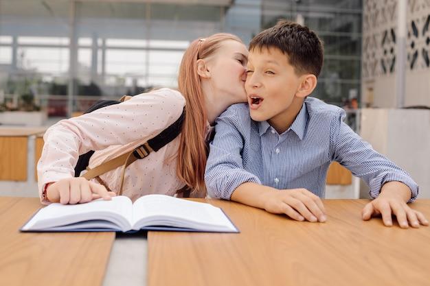 Teenager-schulmädchen flüstert dem jungen etwas ins ohr oder küsst ihn. erste liebe