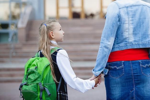 Teenager-schulmädchen in uniform mit einem rucksack in der hand mit mutter, geht die schritte zur schule. rückansicht.